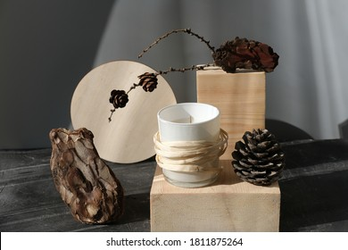 scented candle with forest fragrance on wooden pedestal. fragranced aromatic candle on a natural podium with pine bark pine cones. home scents for freshness and winter mood.