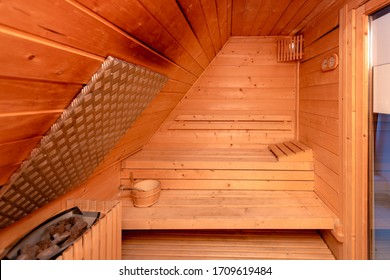 Scented sandalwood small sauna home spa with wooden headrest and thermometer on the wall