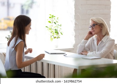 Sceptic or bored aged HR manager listens young vacancy applicant at job interview sit at desk in front of each other, bad first impression, unconvincing inappropriate, unqualified candidature concept