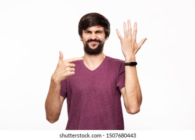 Sceptic brunet bearded man with moustaches pointing at smart watches. Using modern technologies in everyday life.