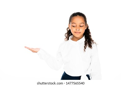 sceptical african american schoolgirl pointing with hand isolated on white