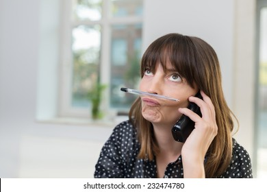 Sceptical businesswoman pulling a thoughtful rueful expression sitting talking on a phone in the office, close up view