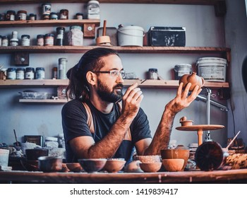Sceptical hardworking man is looking at his own work, ceramic teapot.