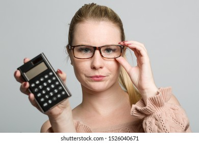 sceptical looking woman with a calculator in her hand