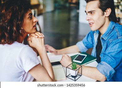 Sceptical young man dressed in denim jacket solving problem with caucasian hipster girl having meeting in modern cafe interior.Confused boyfriend talking with girlfriend about relationship