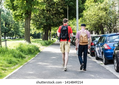 Schaerbeek, Brussels / Belgium - 05 30 2019: Young tall man in shorts and middle aged man with a hat walking through a green street in the Monplaisir borrow