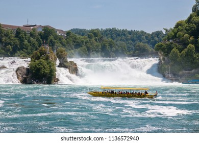 Schaffhausen, Switzerland - June 22, 2017: Boat with people floating to the waterfall the Rhine Falls. It is one of the main tourist attractions. Summer day with blue sky. Print poster, image, photo