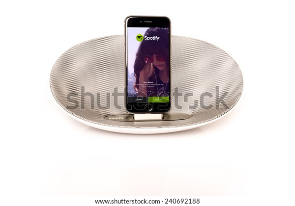SCHARNHAUSEN, GERMANY - DECEMBER 29, 2014: Front view of an Apple iPhone 6 in a Philips docking station and speaker running the Spotify music streaming service with reflection on a white background on