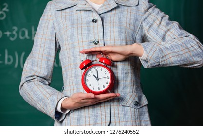 Schedule and regime. Alarm clock in female hands close up. Teachers attributes. Alarm clock in hands of teacher or educator classroom chalkboard background. School discipline concept.