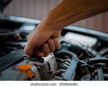 Scheduled maintenance of the car A car service specialist performs the procedure for changing the oil in the car