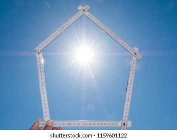 Schematic representation of a house from a folding rule with captured sun