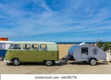 Scheveningen beach, the Netherlands - May 21, 2017: Green VW kombi camper wagen and teardrop trailer at Aircooled classic car show