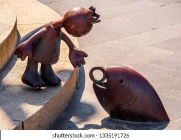 Scheveningen, The Hague, Netherlands. July 2018: tourists and vacationers, as well as bronze sculptures by the sea by American sculptor Tom Otterness on Scheveningen beach