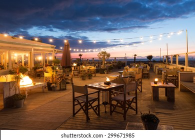 SCHEVENINGEN, THE NETHERLANDS - APR 30:  Sea sunset with eating people in a restaurant with terrace along the Dutch coast on April 30, 2015 Scheveningen, The Netherlands