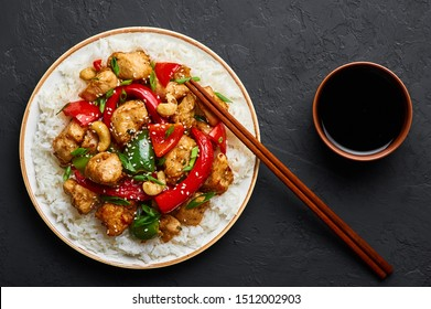 Schezwan Chicken or Dragon Chicken with basmati rice at black slate background. Szechuan Chicken is popular indo-chinese spicy dish with chilli peppers, chicken and vegetables.
