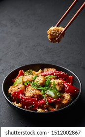 Schezwan Chicken or Dragon Chicken in black bowl at dark slate background. Szechuan Chicken is popular indo-chinese spicy dish with chilli peppers, chicken and vegetables.