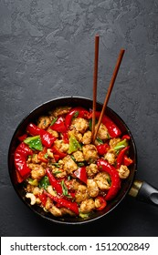 Schezwan Chicken or Dragon Chicken at black slate background. Szechuan Chicken is popular indo-chinese spicy dish with chilli peppers, chicken and vegetables.