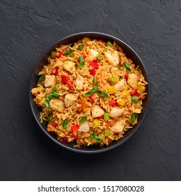 Schezwan Chicken Fried Rice in black bowl at dark slate background. Szechuan Rice is indo-chinese cuisine dish with bell peppers, green beans, carrot, chicken breasts. Copy space. Top view