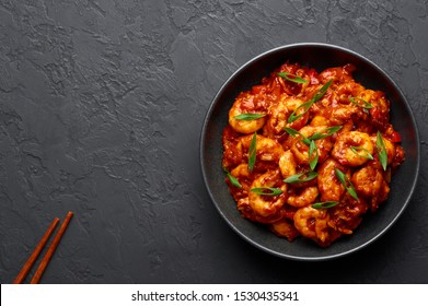 Schezwan Prawns in black bowl at dark slate background. Schezwan Prawns is indo-chinese cuisine curry dish with prawns or shrimps roasted in Schezwan Sauce.