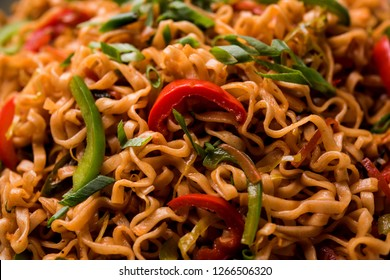 Schezwan veg noodles is a spicy and tasty stir fried flat Hakka noodles with sauce and veggies. served with chopsticks. selective focus