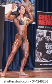 SCHIEDAM, THE NETHERLANDS - APRIL 26, 2015: Female bikini model, power amazon & muscle lady Maria Wattel shows her front double biceps pose at the 38th Dutch National Championship Bodybuilding&Fitness