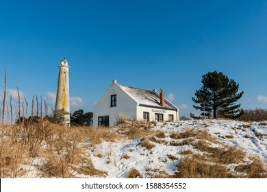 Schiermonnikoog, Friesland/The Netherlands - 02-28-2018: The house  at the old Southern lighthouse surrounded by snowy dunes.