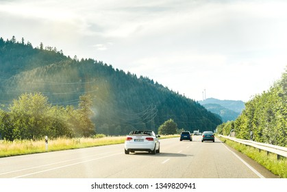 Schiltach, Germany - Jun 10, 2018: German highway with luxury Audi convertible cabriolet car driving fast on the rural highway on a sunny day with Black Forest mountains in background