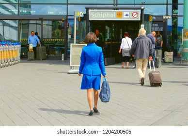SCHIPHOL AIRPORT, NETHERLANDS - October 21, 2017. Stewardess of KLM and other tavelers are walking outside in sunshine to the main entrance terminal building.