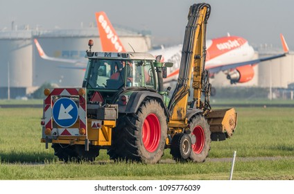 Schiphol, N-H/Netherlands -May 09-05-18- Excavator is driving at the airport underway to his job. Airplane from Easyjet is landing at the background of the image.