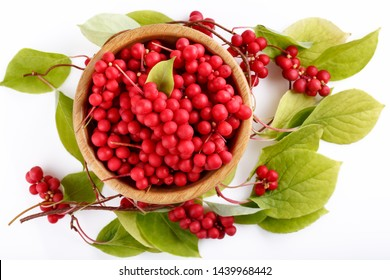 Schisandra chinensis or five-flavor berry. Fresh red ripe berries with leaves in wooden bowl on white background. Top view.