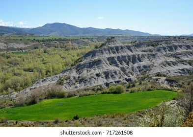 The schistose cliff is surrounded with a narrow green field and spring woods in the Spanish region Navarra. This is unusual geological formation of metamorphic rock.