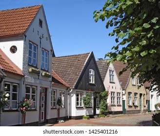 Schleswig, Germany - July 19, 2012: Street in Holm - historical fisherman's quarter in Schleswig with old 18th century houses. Popular tourist destination in Schleswig-Holstein, North-West Germany
