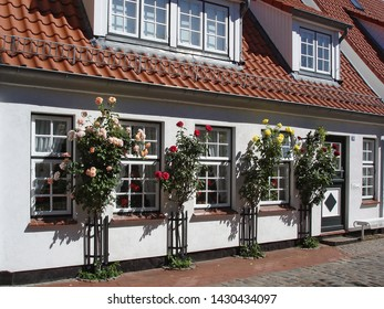 Schleswig, Germany - July 19, 2012: Facade of the small house decorated with flowers. Historical fisherman's quarter Holm in Schleswig city, Schleswig-Holstein, North-West Germany