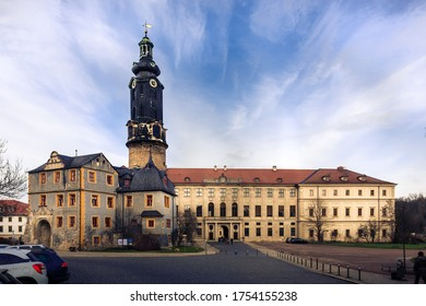 The Schloss Weimar surrounded by cars under the blue cloudy sky in Weimar, Thuringia, Germany