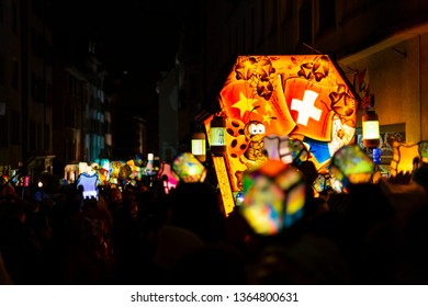 Schneidergasse, Basel, Switzerland - March 11th, 2019. Close-up of a carnival group marching in the old town with their illuminated main and head lanterns.