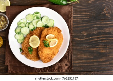 Schnitzel and cucumber salad on plate over wooden background with copy space. Top view, flat lay.