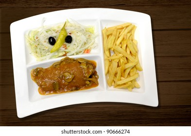 Schnitzel with mushroom cream sauce, cabbage salad and french fries