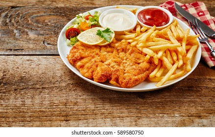 Schnitzel on white dish served with French fries potatoes, sauces and vegetable salad, on rough wooden table surface with cutlery on red napkin. Copy space