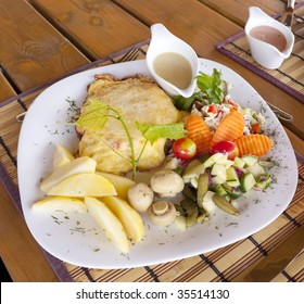 Schnitzel served with vegetables on a white plate