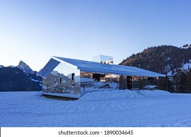 Schoenried, Switzerland - December 18, 2020: The Swiss Alps landscape reflected in blue hours on Mirage Gstaad by the American artist Doug Aitken