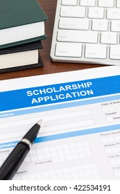 Scholarship application form with pen, keyboard, and text book