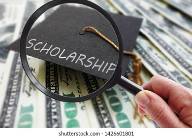 Scholarship graduation cap on money with magnifying glass