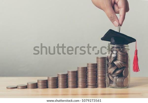 Stipendiengeld-Konzept. Hand von Männern oder Frauen, die Münzen in Glar stecken mit Geldstapel steigende Erhöhung des Wachstums sparende Geldinvestition