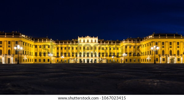 Schonbrunn Palace at night in gold light illumination. Low, wide angle perspective. Vienna, Austria, 25 March 2017