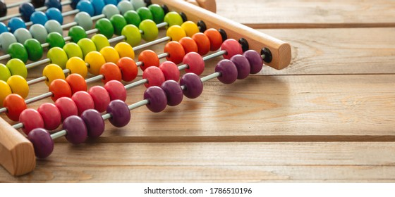 School abacus with colorful beads on wooden desk, close up view, copy space. Kids learning count, children math class concept