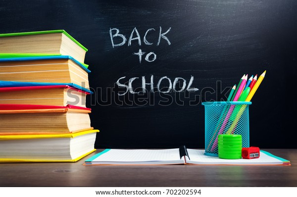 school accessories on the table with blackboard background. Pencils and books
