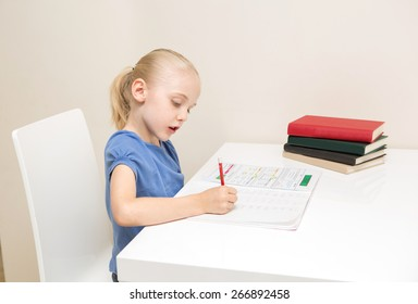 School Age girl with blond hair studying on white table against white table.