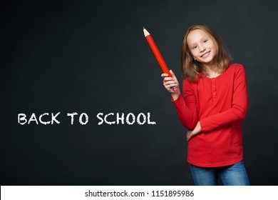 School age girl holding big pencil and drawing or writing on blank copy space for text. Back to school concept.