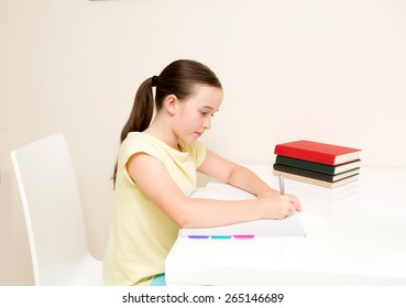 School age girl studying home work on white table on a white chair