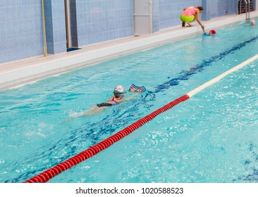 School age girl swims in pool with board. Young children swimming training in Russian sports school